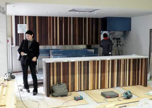 ダイハツ工業社員寮「パリオ花屋敷」、大利木材の端材を使って壁の意匠を施工中。エンバディデザイン、都市デザインシステム